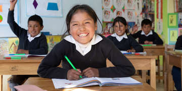 10-year-old Peruvian girl smiles for the camera, as she sits at her desk among other children in a classroom in Casapata, Peru. Photo credit: Save the Children / Jordan J. Hay, 2018.