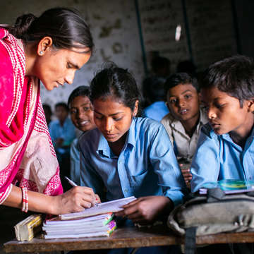 "10-year-old Mamta, right, reviews a math problem with her teacher during a class lesson on Tuesday, May 1, 2018 in the Sarlahi region of Nepal. Mamta is currently attending the third grade, two years behind for her age, resulting in not enough support earlier in her education. Currently in Mamta's community the kindergarden, first grade and preschool are all combined. ""If Save the Children can help me finish my studies, that would be nice,"" Mamta said. Photo credit: Victoria Zegler / Save the Children 2018."