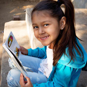 Surena, 4, reads during a home visit as part of Save the Children's signature Early Steps to School Success program in Central Valley California. Photo credit: Tamar Levine / Save the Children 2017.