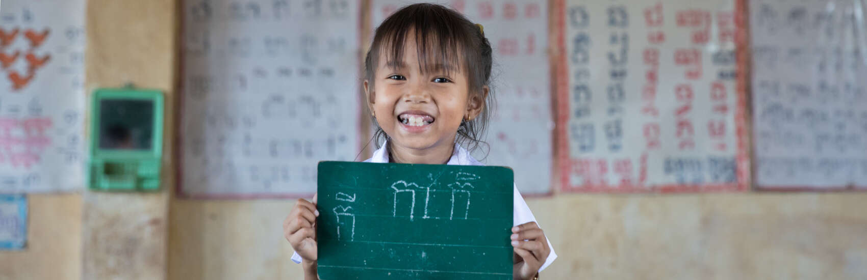 Little Monyrath, age 7, one of our First Read program students, stands at the front of her classroom, proudly holding a mini chalkboard displaying her work.
