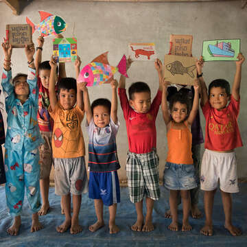 Children stand with their hands above their heads, happily holding favorite books and drawings.
