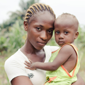 A mother holds her young African child, who suffered with pneumonia but was helped to recover, near a road in the Democratic republic of Congo.
