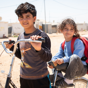 Young brothers take a break from a bicycle ride around the refugee camp where they live in Jordan.