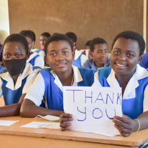A young female student, Christabel, displaying a thank you placard for Save the Children donors to Malawi.