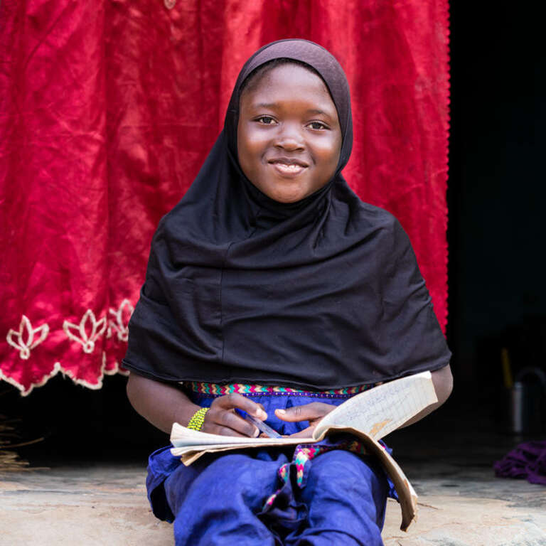 Awa, age 10, sits and smiles in her home's doorway, covered by a bright red curtain, while working on her homework.