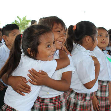 Two girls from Mexico are smiling and hugging each other.