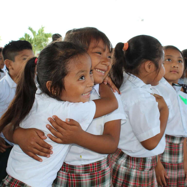Two young girls from Mexico in their school uniforms happily hug each other.