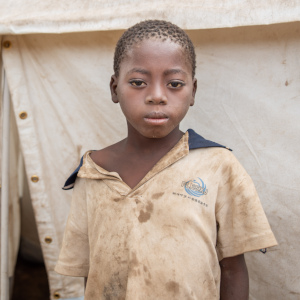 A ten-year old African child who lost his home when Cyclone Idai hit stands near a tent in Mozambique.