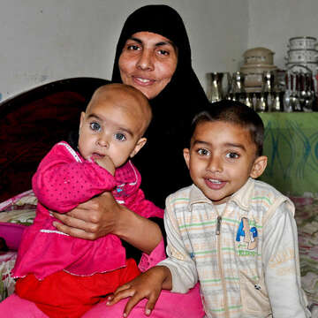 Mother Sobia smiles while sitting with her children Fatima, age 9 months, and Abdullah, age 3, inside their home in Pakistan.