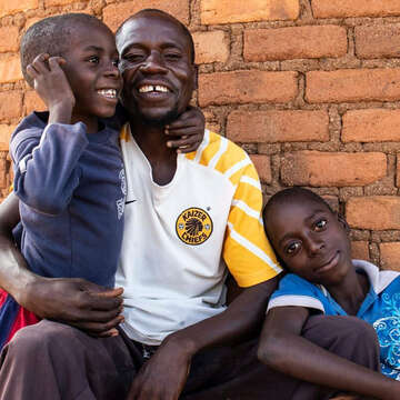 Ntokozo from Zimbabwe smiles as he embraces his sons Joseph, age 7, and Sipho, age 13.