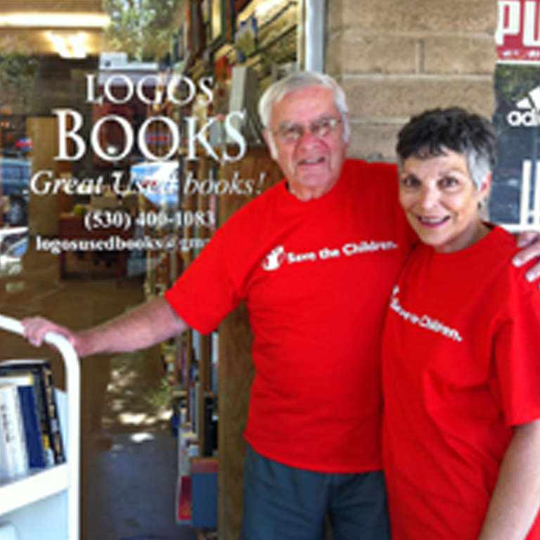 Donors Peter and Susan Linz stand in front of their bookstore wearing Save the Children t-shirts. Photo credit: Save the Children, May 2011.