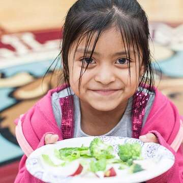 Young girl holding a plate of broccoli.