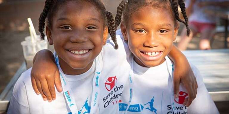 Two girls wearing Save the Children shirts smile at the camera.