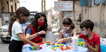 Children play a game with a Save the Children representative in Lebanon.