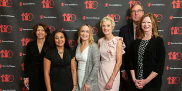Six member of Save the Children's Boston Leadership Council Benefit pose in front of a patterned background printed with the Save the Children logo. The men and women are attended a benefit at the Downtown Harvard Club hosted by Tim Douglas. Photo credit: Casey Atkins/Nov 2018.