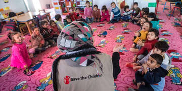 A woman wearing a Save the Children branded shirt sits with a group of children in a circle.
