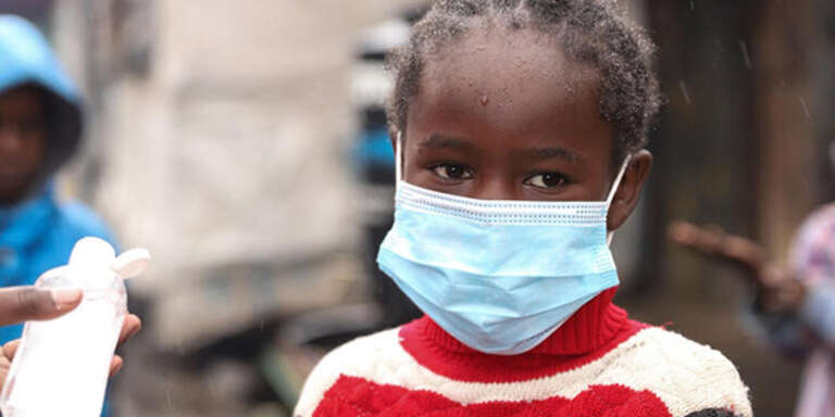 A young girl in Kenya wears a face mask while applying hand sanitizer to help prevent the spread of COVID-19.