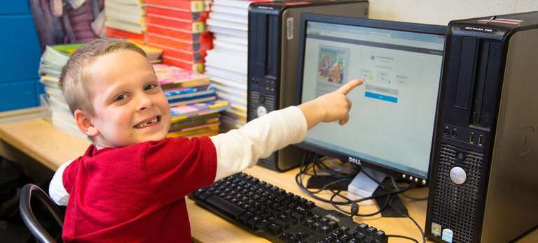 A boy points at a computer in a classroom