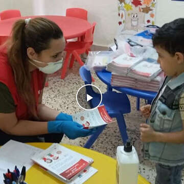 A woman wearing a mask shows a child a coronavirus pamphlet