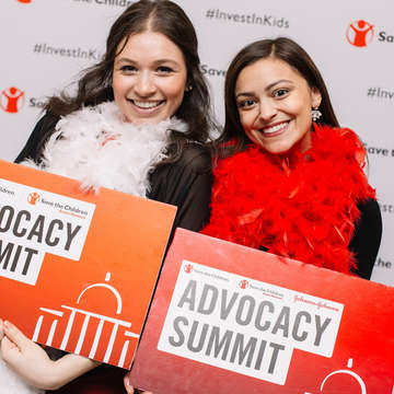 Two Save the Children staff members hold red signs that read, Advocacy Summit: while standing in front of a white mural with Save the Children's logo and the hashtag #InvestinKids printed on it. Photo credit: Rachel Couch/ Save the Children, March 2019.