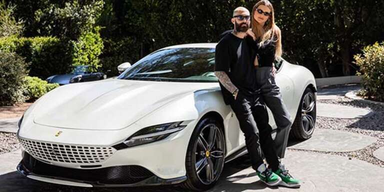 Adam Levine and Behati Pinsloo stand in front of a white Ferrari.
