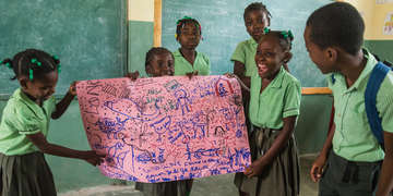 A group of children explain a picture that they drew showing what they experienced during Hurricane Matthew, at the Child Friendly Space at a school. Photo credit: Ray-ginald Louissaint Jr / Save the Children 2018.