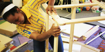 This photo was taken by Laura Gomez, Communications Manager, U.S. Programs, in April 2018. The pictured IKEA iWitness trip participant is assembling furniture as part of a childcare center renovation project. The center was damaged after Hurricane Harvey, and IKEA provided supplies and support to update one of their classrooms, to allow the center to build back to full capacity. Photo credit: Laura Gomez/Save the Children 2018.