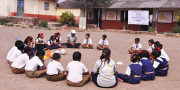 A group of children sit on the ground in a circle at a school in Induri, Maharashtra, India. Their attention is on a teacher. These play sessions are sponsored by Mondelez, and involve learning nutrition and playing games to reinforce a positive message about exercise and good nutrition. Photo credit: Luciana Bonifacio / Save the Children, November 2015.