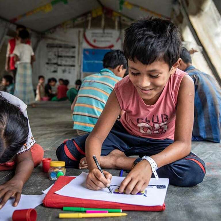 A smiling boy sits on the ground while doing school work.