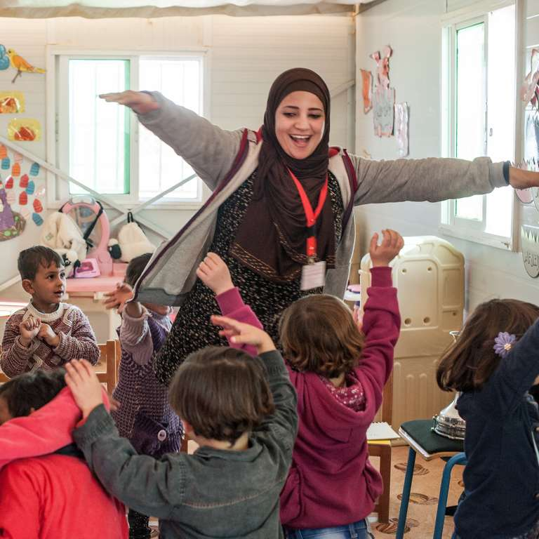 A kindergarten teacher leads her students in a music activity at a Save the Children Rainbow Kindergarten for refugee children. Every classroom runs a Healing and Education Through the Arts (HEART) activity daily. Photo credit: Susan Warner/Save the Children, December 2016.