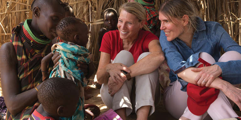 Carolyn Miles, President & CEO of Save the Children, sits outdoors surrounded by mothers and children in Turkana County, Kenya. She smiles at a young baby, as the mothers tell her how the drought is affecting the children of the village. Photo credit: Peter Caton/Save the Children, July 2017.