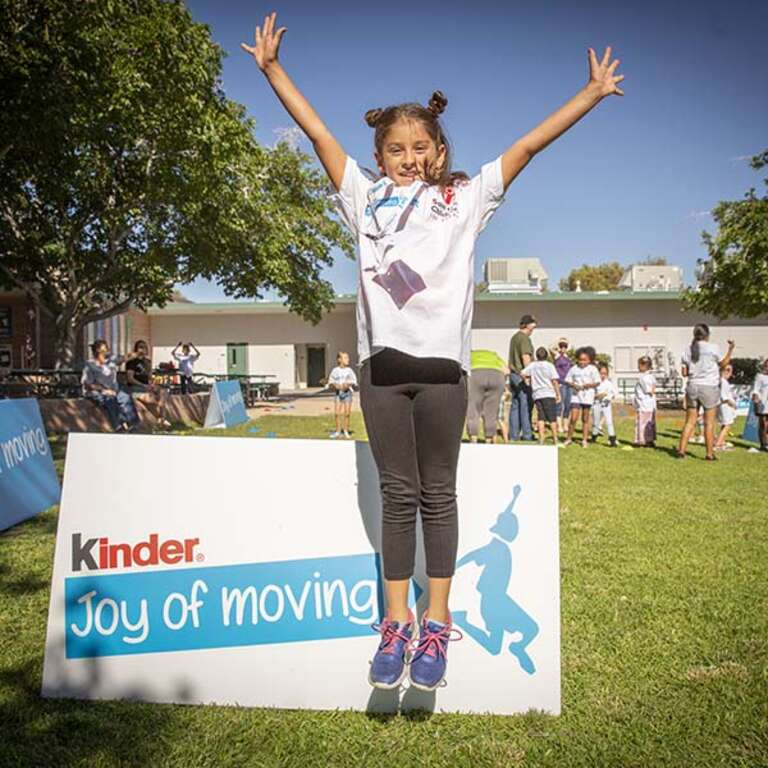 A girl jumps with her arms raised in front of a sign for Kinder Joy of Moving.
