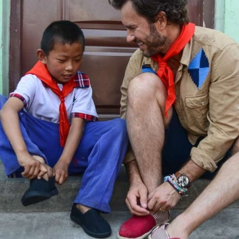 "TOMS' Founder and Chief Shoe Giver, Blake Mycoskie, shares a special moment with a student in a school for migrant children while in Beijing for the company's annual ""One Day Without Shoes"" awareness campaign. Photo Credit: TOMS' 2015."