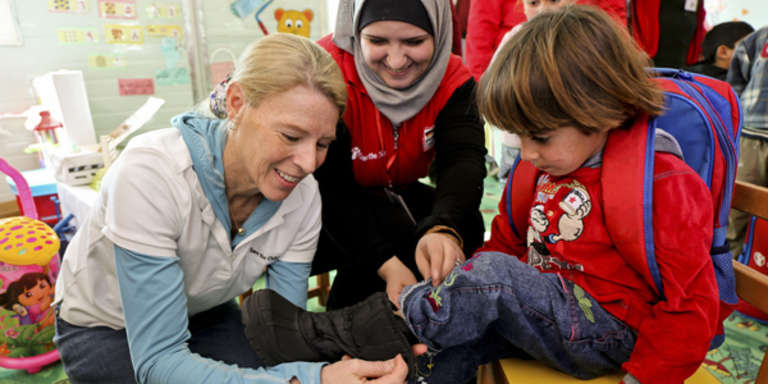 Carolyn Miles, CEO and president of Save the Children helps a child in one of our child-friendly spaces put on a new pair of boots donated by TOMS at Za'atari refugee camp, Jordan. Photo Credit: Save the Children/Suzanna Klaucke 2014.
