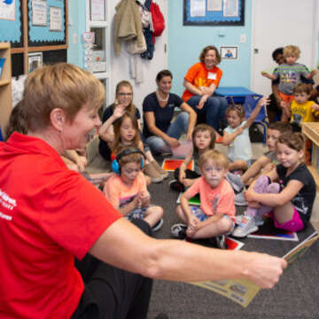 A GSK employee wearing a red Save the Children t-shirt reads to children at a child care center in Wilmington, DE. The center was significantly damaged by Hurricane Florence in September 2018 and Save the Children has supported its operations and recovery since the earliest days of the storm. Photo credit: Eric Atkinson/Save the Children, May 2019.