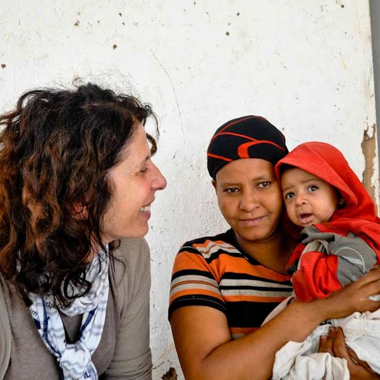 Michelle Daum, left, talks with a mother and child as she visits a Save the Children program in Ethiopia. Photo Credit: Save the Children 2012.