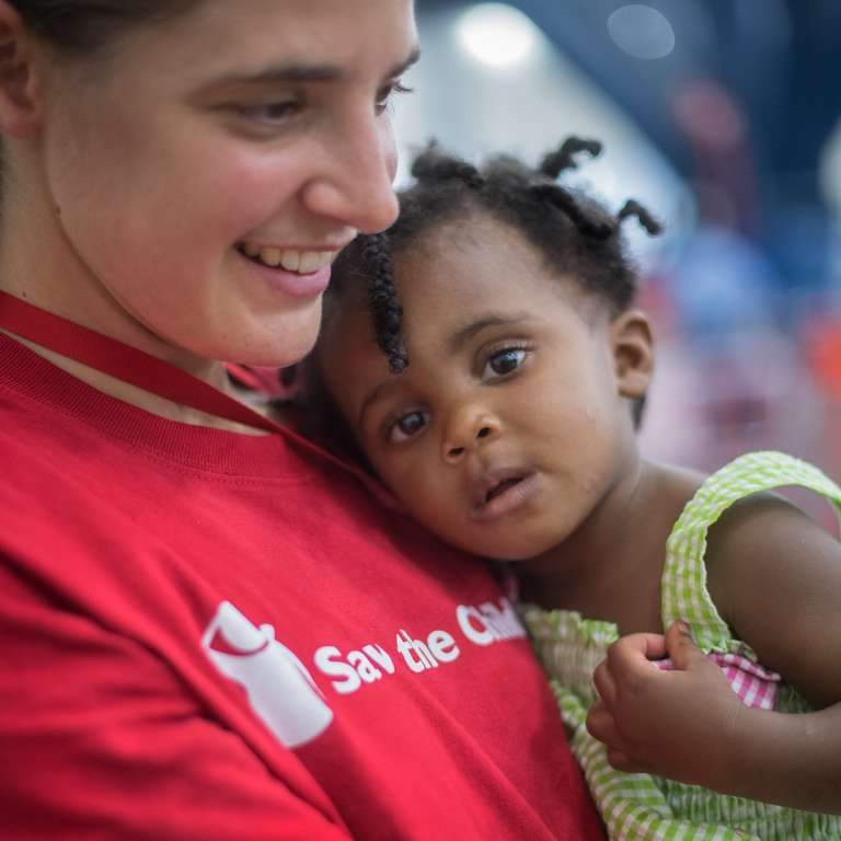 Save the Children Bruderhof volunteer Rose Mommsen holds a 2-year-old Layna* in the mother-baby space in the George R. Brown convention center shelter in Houston Texas. Photo Credit: Susan Warner/Save the Children 2017.