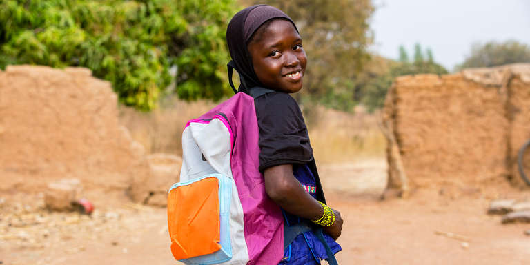 A 10-year-old girl carries her backpack to her school in Mali. The girl participates in Save the Children's Literacy Boost, which aims to enhance early reading. Photo credit: Victoria Zegler/Save the Children, Jan, 2018.