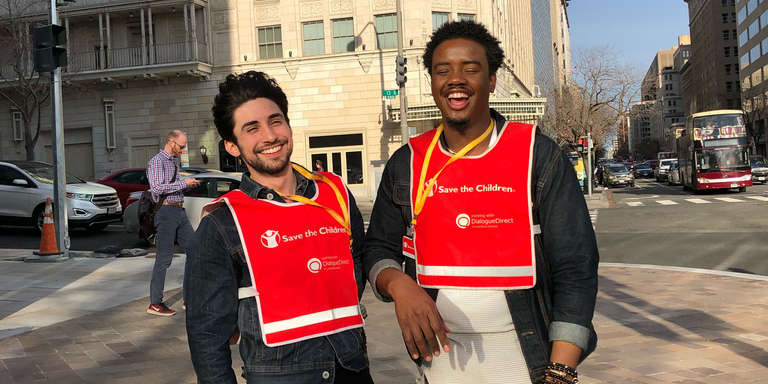 Two canvasers from DialogueDirect stand on a street in Washington D.C. smiling fundraising for Save the Children.