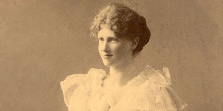 An early, sepia-toned photo of Save the Children's founder, Eglantyne Jebb. Jebb is dressed in a ruffled, feminine dress, but she kneels on an ornate, wooden armchair – rather than sitting demurely –indicative of her defiant nature. Photo credit: Save the Children.