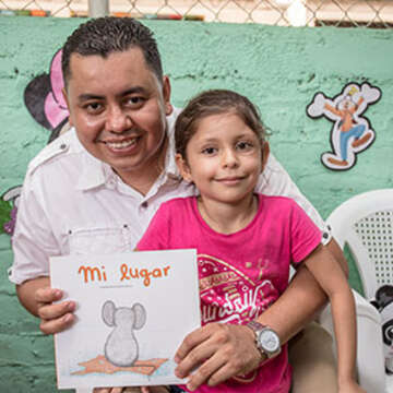 A father and daughter hold a children's picture book while standing together in front of a green mural decorated with characters.