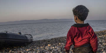 A young boy looks out to sea from the shores of the Greek island of Lesvos. Next to him is an inflatable boat.