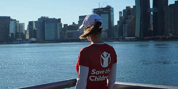 Woman in a Save the Children shirt standing before a skyline