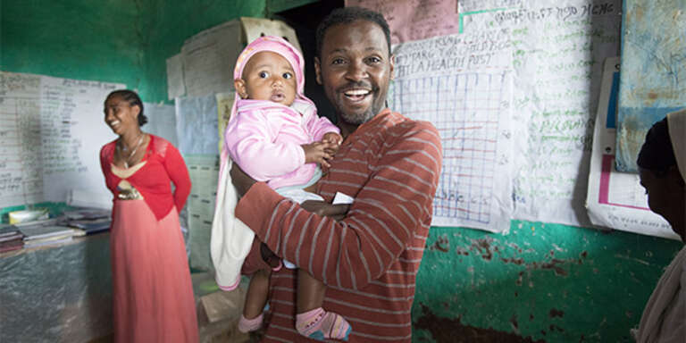 A father in Ethiopia smiles widely as he holds his baby who wears a pink blanket and hat