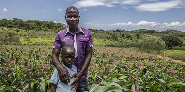 A father stands with his son in a field in Mozambique where he works to support his family