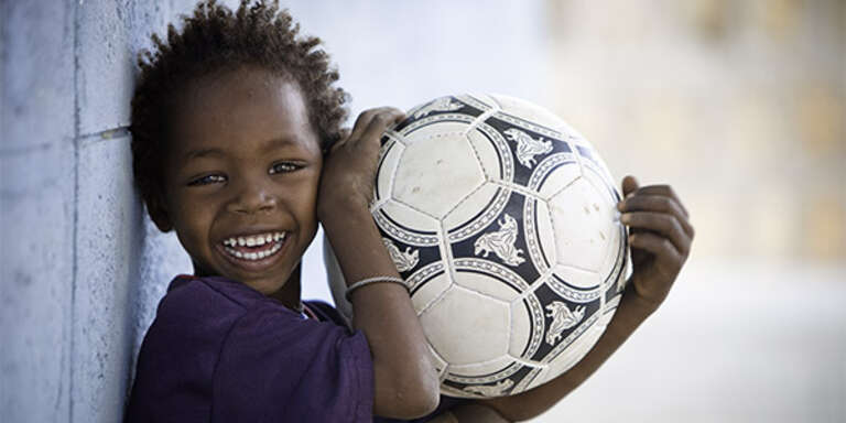 A boy in Ethipioa holds a soccer ball and smiles.