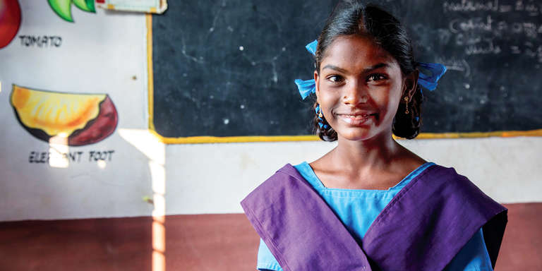 In a classroom in India, a 13-year old girl stands in front of a chalk board and bright posters depicting the English word for various fruits and vegetables. The girl was previously out of school because her family needed her to help earn income, however, a Save the Children community worker helped support the girls' return to learning and now she is a top-of-class student. Photo credit: Rajan Zaveri / Save the Children, Jan 2019
