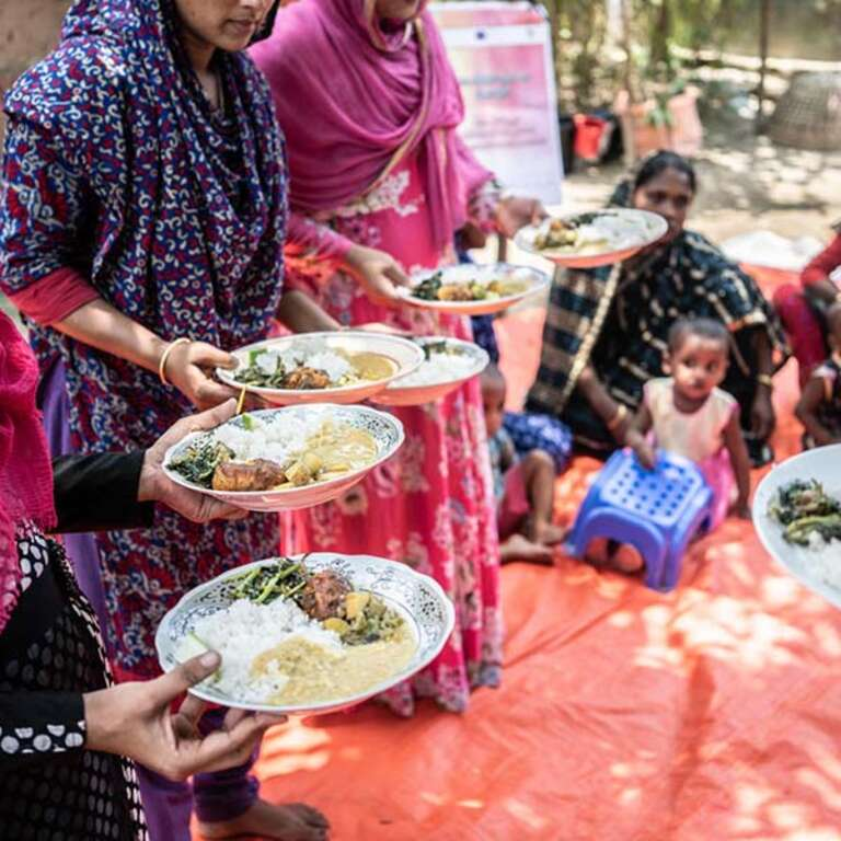 A group of women holding plates of food.