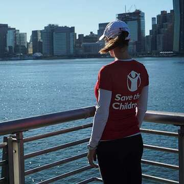 A woman in a Save the Children shirt looks over the water.