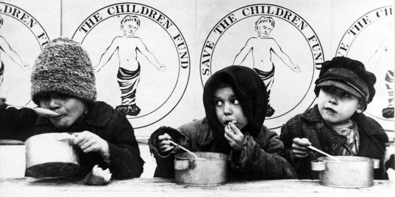 "An early black-and-white photo depicts three young children hungrily spooning soup out of tin bowls. The children are bundled up in winter coats and hats; behind them are posters featuring a rudimentary logo for ""Save the Children Fund."" Photo credit: Save the Children."